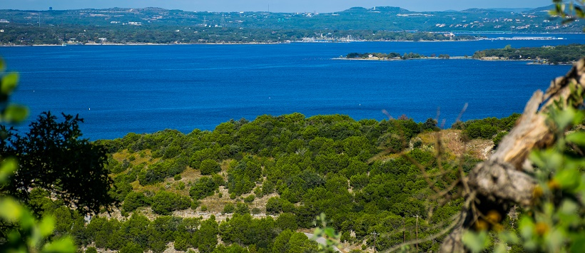 View of bright blue water at Lake Travis surrounded by vibrant green Hill Country.