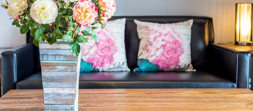 Wooden vase with colorful flowers on table in front of black couch with floral pillows.