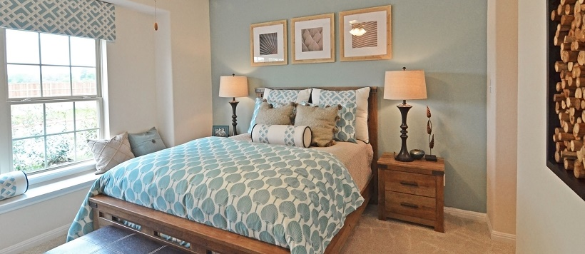 Light blue and white bedspread and pillows with light blue accent wall in South Austin home bedroom.