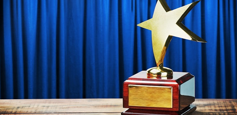 Star trophy on wooden table in front of blue curtain.