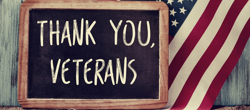 """American flag hangs behind a chalkboard sign reading """"Thank You, Veterans"""" for Austin Memorial Day events."""