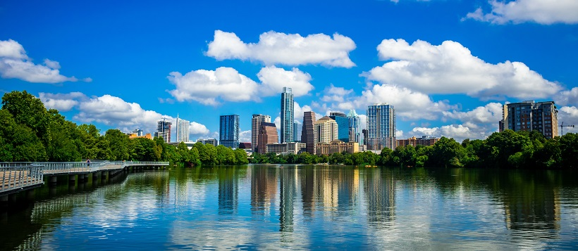 Vibrant blue sky filled and white clouds over an Austin skyline reflected in Lady Bird Lake.