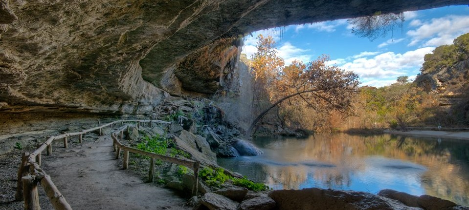 Rock formations create a roof over a walkway that circles around the water at Hamilton Pool.