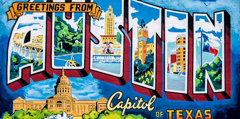 Colorful mural reading 'Greetings from Austin Capitol of Texas' for a moving announcement picture.