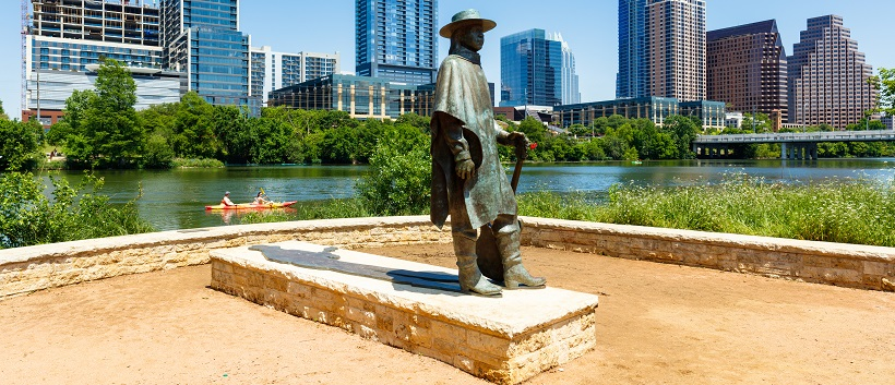 Stevie Ray Vaughan statue with Austin skyline and kayaker in the background.