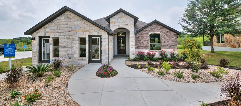 Landscaped yard and sidewalk lead up to a stone and brick front exterior of a one-story home.