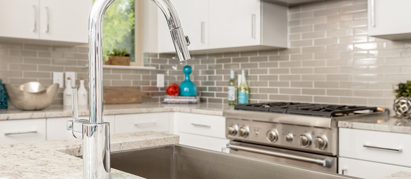 Close up of silver faucet over deep sink with stainless steel oven in the background of kitchen.