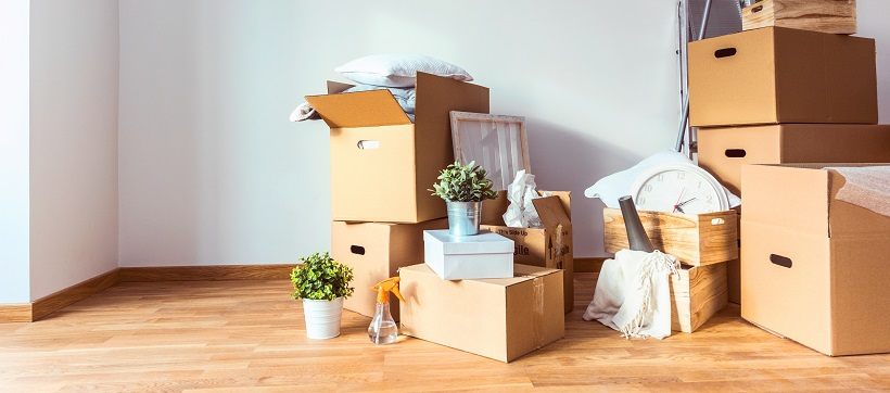 Cardboard boxes filled with items are stacked in the corner of an empty room.