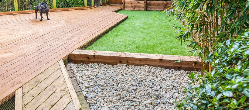 Gravel pathway and dog standing on wooden porch to show dog-friendly landscaping ideas.