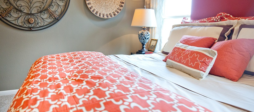 Close up of orange and white bedspread on bed at The Hills of Bear Creek.
