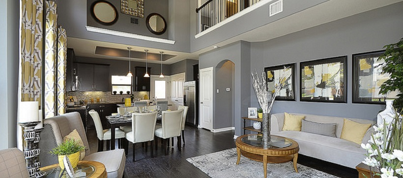 Walls with gray paint surround the living room of an open-concept home as it leads into a dining room and then the kitchen.
