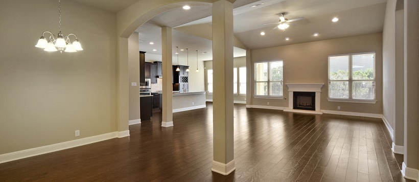 Hardwood floors of a blank open-concept home lead into the kitchen.