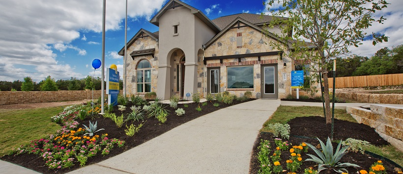 Beautiful front exterior of a landscaped front yard that leads up to two-story home.