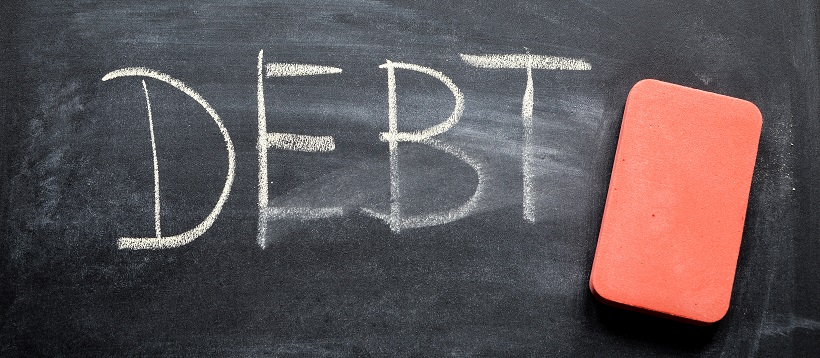 "Next to a pink eraser, the word ""DEBT"" is written on a chalkboard that has been slightly erased."