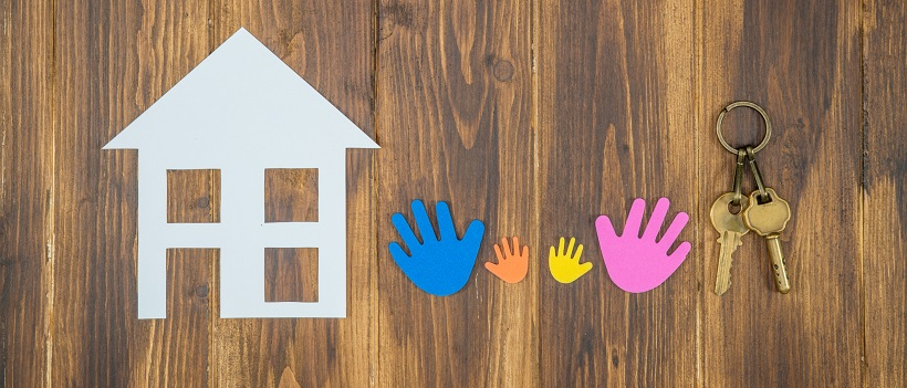 White paper home next to colorful paper hands and keys on a wooden background.