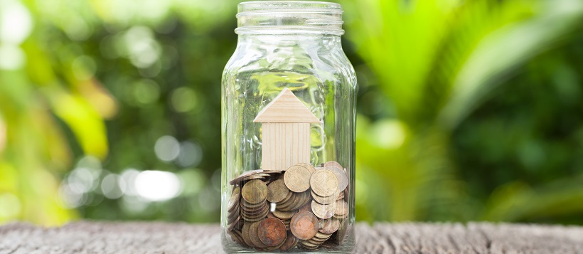 Mason jar sitting on table outside filled with change and a small wooden house.