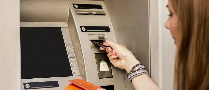 Woman putting credit card into ATM.