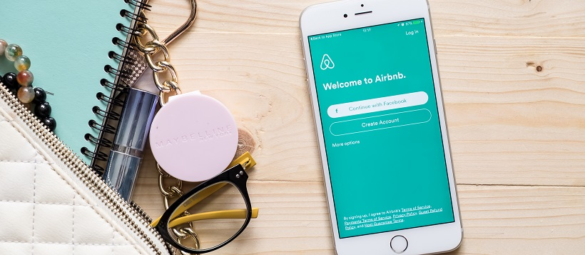 Purse with contents spilled out next to smartphone showing Airbnb screen.