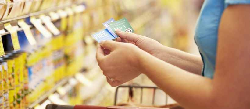 Close up of woman holding coupons while shopping at the grocery store
