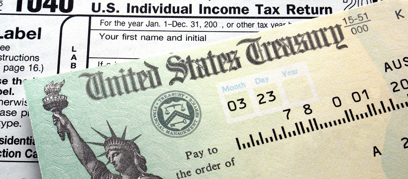 Tax refund check on top of income tax return form.