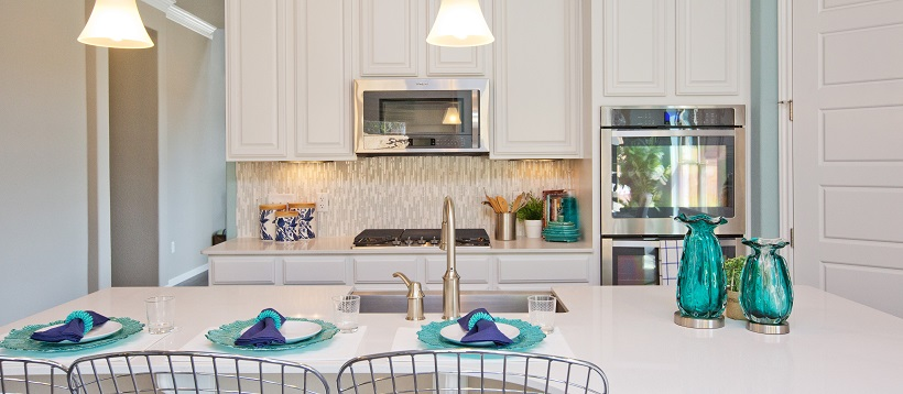 White home decor shown with white cabinets in a contemporary kitchen with blue accent pieces.