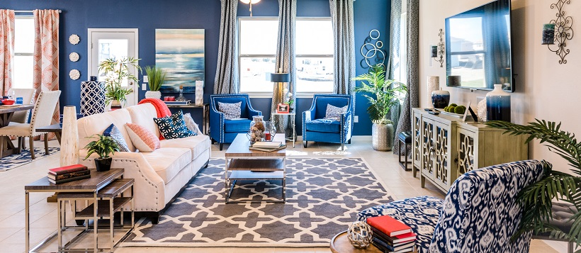 Vibrant living room with a white couch, blue accent wall, and various blue and white home decor pieces.