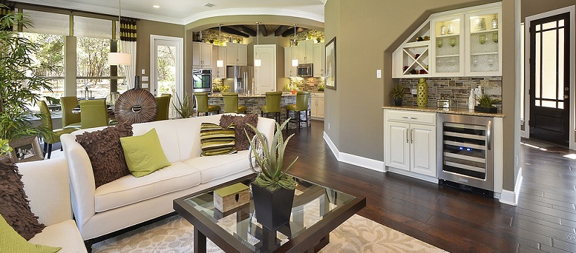 Living room with white couches and brown and yellow pillows on top of deep brown hardwood floors.