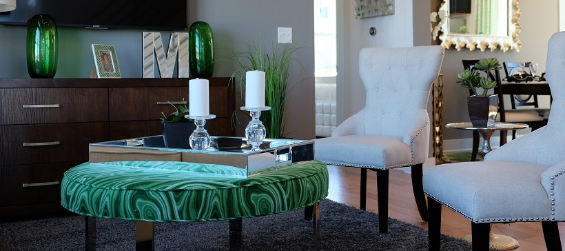 Living room seating area with white armchairs and a green ottoman.