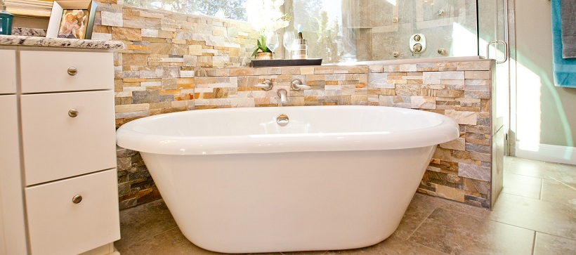 Luxurious bathroom with white porcelain tub surrounded by a stone tiled backsplash.
