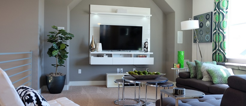 Media room with gray walls and a white modern decor piece surrounding the television.