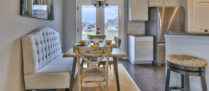 Rustic breakfast area with French doors in the background and near a white kitchen.