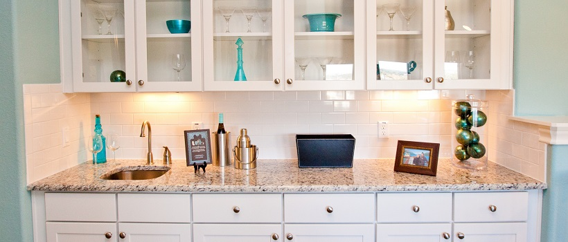 Bar area with white cabinets, granite, and blue home decor pieces inside the cabinetry.