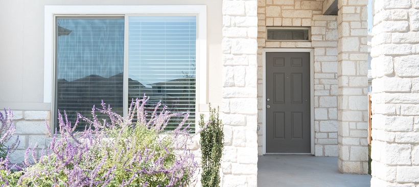 Front home exterior with a window surrounded by white stone leading to the front door.