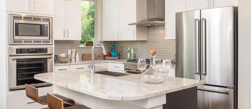 White modern kitchen with stainless steel appliances and white granite on center island.