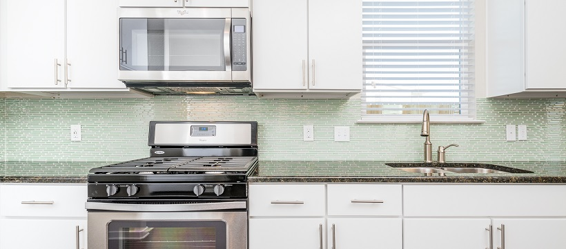 Kitchen with white contemporary cabinetry, stainless steel appliances, and a green backsplash.