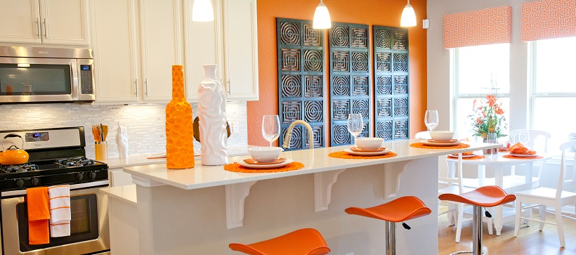 Modern kitchen with white cabinets and white home decor ideas as well as orange accents and stools.