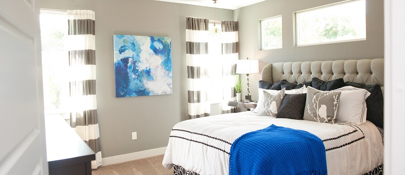 Gray walls surround a large bed with a white bedspread with black accents.