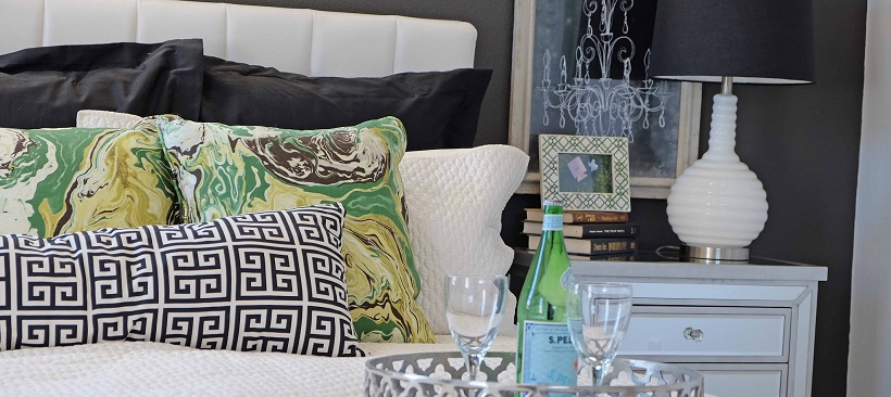 Close up of bed with white bedspread and headboard with black and green pillows between.