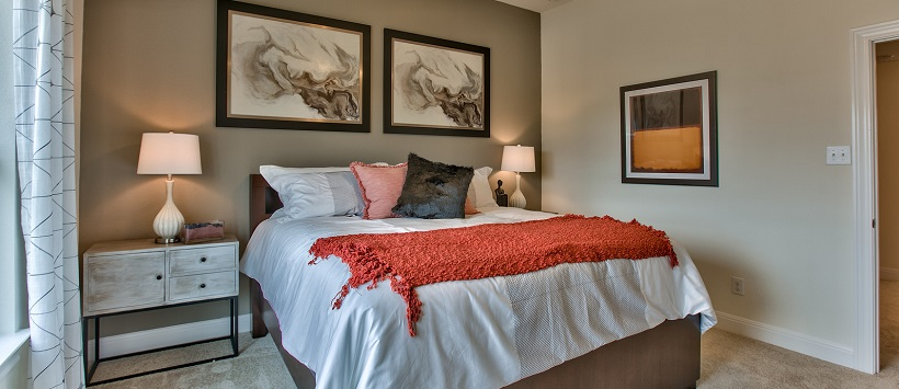Bed with white bedspread and orange throw in front of tan accent wall.
