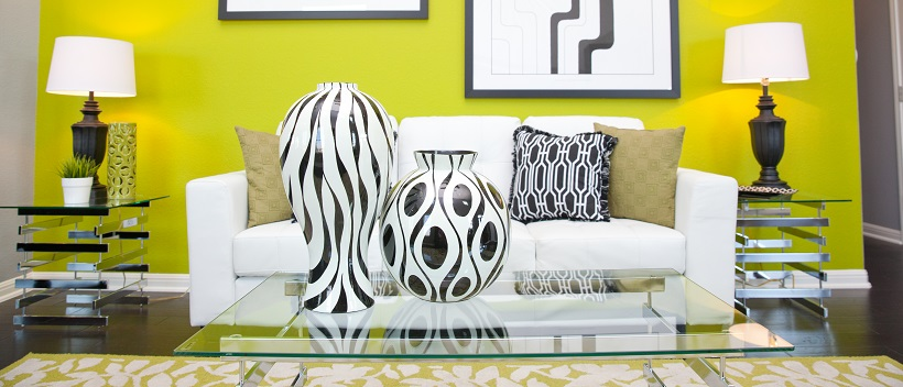 Black and white home decor ideas placed on glass table in front of white couch with vibrant yellow accent wall in the background.