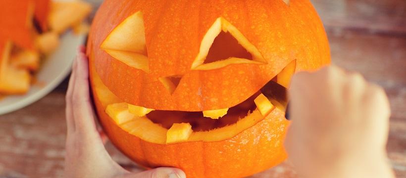 Close-up of person carving a face into a pumpkin as an outdoor entertainment idea.