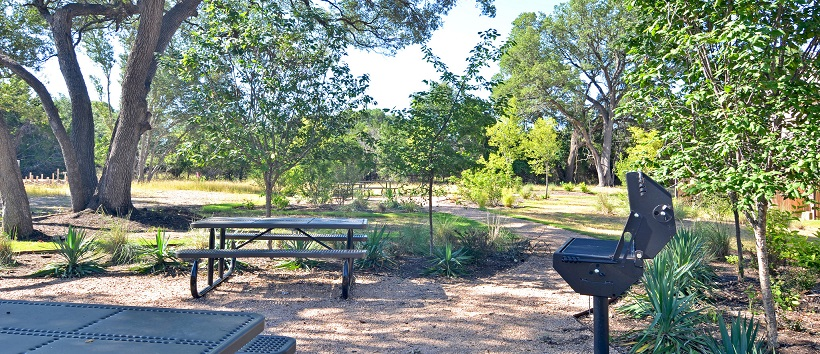 Picnic area with tables and trees near a MileStone community.