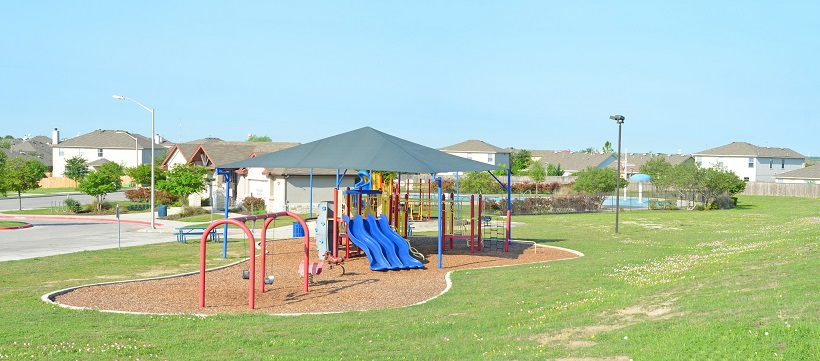 Shadow Creek's playscape surrounded by lots of grass.