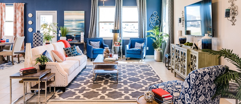 An inventory home with a vibrant living room with a blue accent wall, blue chairs, and red accent pieces.