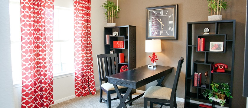 Study with red and white drapes next to a brown accent wall behind bookshelves and a desk.