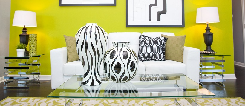 Behind white and black vases sits a white couch in front of a vibrant yellow wall.