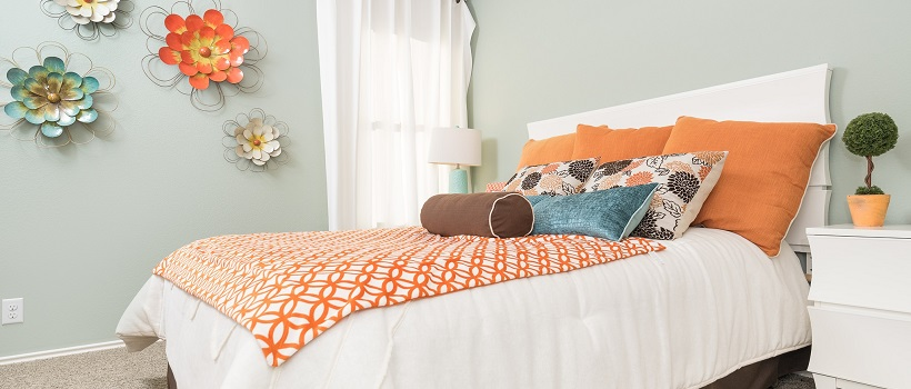 A gray-blue painted bedroom with a bed topped by orange blankets and pillows.
