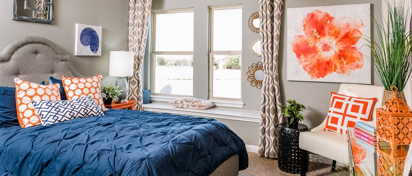 Bed topped by a blue bedspread and white and orange pillows, surrounded by orange and white decor.