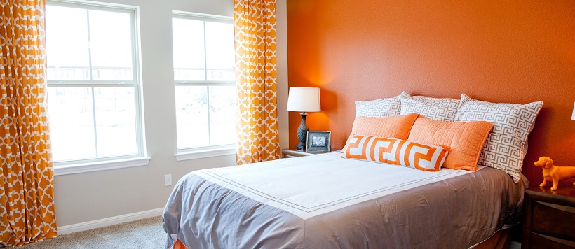 Vibrant bedroom with a gray and white bed, an orange accent wall, orange drapes and orange pillows.