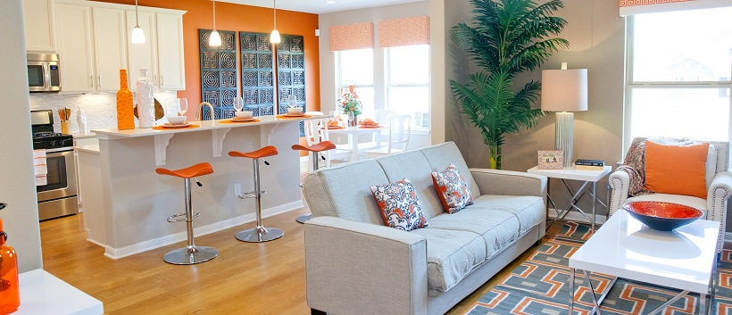 Gray and orange living room in front of a white and orange kitchen.